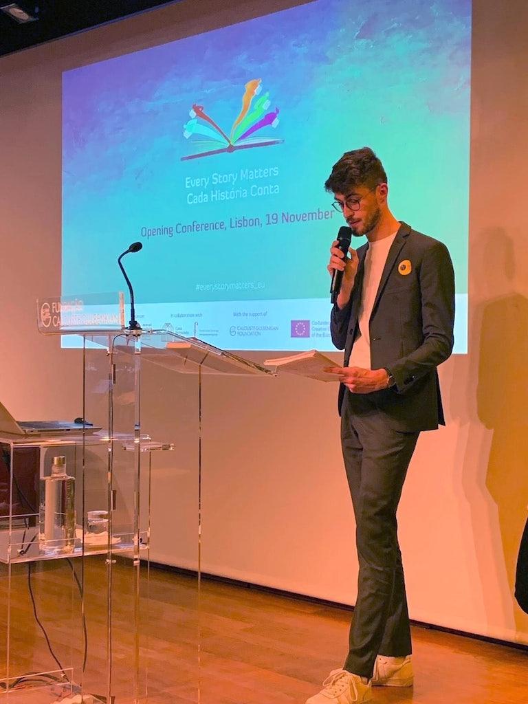 Yannick, vanuit Literatuur Vlaanderen coördinator van Every Story Matters, neemt het woord tijdens de conferentie in Lissabon.